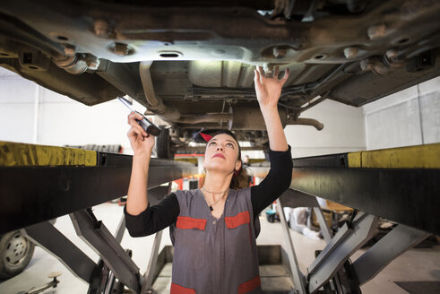 Mechanic woman working under a car with led light - JASF000681