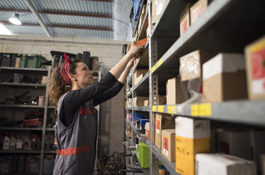 Woman in warehouse, she examines boxes. - JASF000684