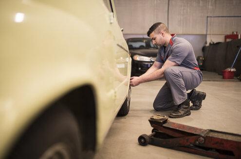 Mechanic repairing car wheel - JASF000696