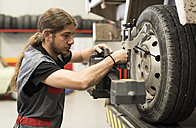 Mechanic calibrating wheels with computer and technology equipment - JASF000699