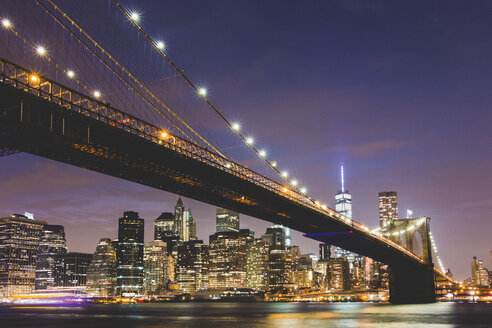 USA, New York City, lighted skyline and Brooklyn Bridge in the foreground at night - GIOF000889