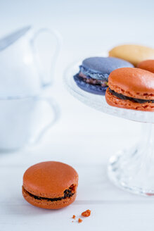 Macarons on a cake stand and a single one on table with crumbs - OJF000135
