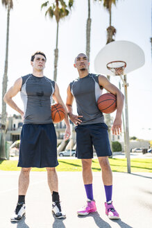 Two young men standing on outdoor basketball court - LEF000094