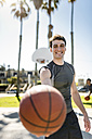 Smiling young man holding basketball on outdoor court - LEF000103