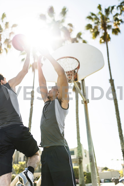 Two young men playing basketball on an outdoor court - LEF000106