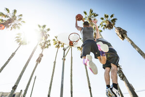 Two young men playing basketball on an outdoor court - LEF000108
