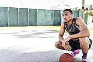 Basketball player crouching on outdoor court - LEF000120