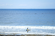 Spain, Tenerife, boy with surfboard in the sea - SIPF000357