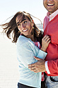 Portrait of smiling woman with blowing hair hugging by her boyfriend - VABF000448