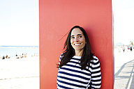 Spain, Barcelona, portrait of woman wearing striped sweater leaning against red panel - VABF000450