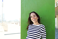 Portrait of happy woman at green wall - VABF000453