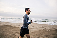 Young man running on the beach - EBSF001297