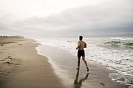 Young man running on the beach - EBSF001306