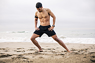 Sportive young man stretching on the beach - EBSF001312