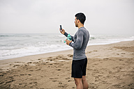 Sportive young man with cell phone and drinking bottle on the beach - EBSF001318