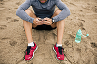 Sportive young man with cell phone and drinking bottle on the beach - EBSF001321