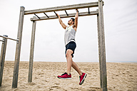 Young man exercising on monkey bars on the beach - EBSF001324