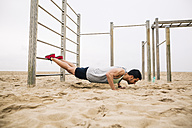 Young man doing push-ups on wall bars on the beach - EBSF001333