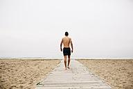 Young man walking on boardwalk on the beach - EBSF001351