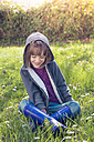 Girl wearing hooded jacket sitting on flower meadow - LVF004776