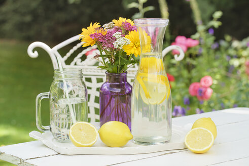Infused lemon water and fresh lemons on summer garden table - ECF001879