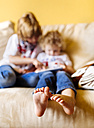 Feet of little boy sitting on couch with his brother, close-up - MGOF001740