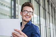 Portrait of smiling young businessman with digital tablet - DIGF000314