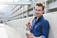 Portrait of young businessman with  digital tablet leaning against wall - DIGF000317