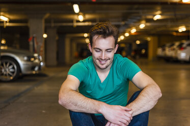 Portrait of smiling young man sitting in underground car park - DIGF000323