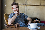 Portrait of happy young man sitting in a coffee shop - DIGF000341