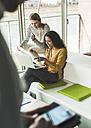 Two women in office using laptop - UUF007081