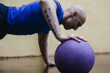 Man doing push-ups with a medicine ball - ABZF000376