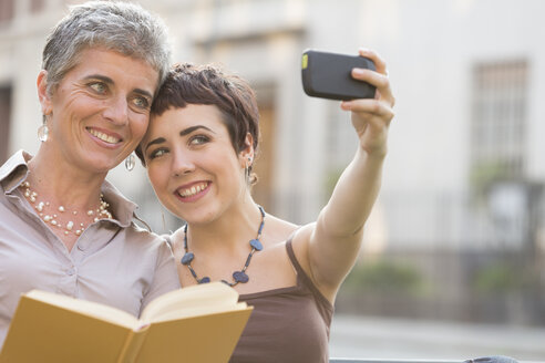 Mother and adult daughter taking selfie with smartphone - ZOCF000034