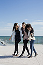 Three young women walking arm in arm by the sea - MAUF000447