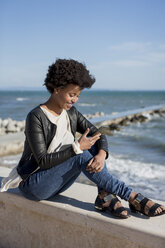 Young woman sitting by the sea, using smart phone - MAUF000450