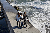 Three young women walking on breakwater at the sea, rear view - MAUF000453