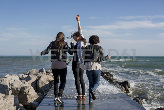 Three young women having fun on breakwater at the sea - MAUF000456