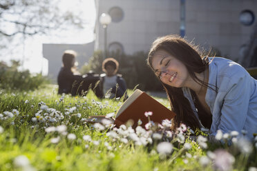 Young woman in park reading book - MAUF000471