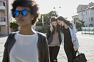 Young woman with sunglasses in the city with her friends - MAUF000474
