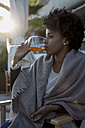 Young woman sitting in bar drinking aperitif - MAUF000489