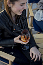 Young woman sitting in bar drinking aperitif - MAUF000492