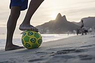 Brazil, Rio De Janeiro, man standing with ball on Ipanema beach - MAUF000495