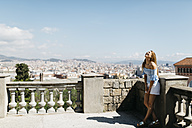 Spain, Barcelona, Young woman enjoying view of the city - JRFF000556
