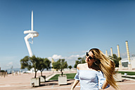 Spain, Barcelona, Young woman walking in the city - JRFF000565