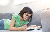 Girl lying on the couch reading a book - LVF004789