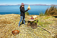 Peru, Titicaca lake, tourist on a floating island holding a miniature reproduction of the Uros reed houses - GEMF000876