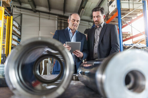 Two engineers with digital tablet in front of hydraulic cylinder - DIGF000352