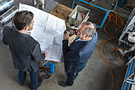 Two engineers with construction plan talking, hydraulic cylinder - DIGF000361