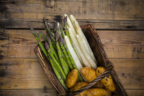 White and green asparagus and new potatoes in wickerbasket - LVF004792