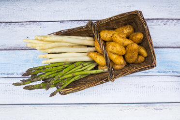 White and green asparagus and new potatoes in wickerbasket - LVF004798